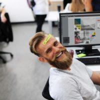 man laughing while working on computer