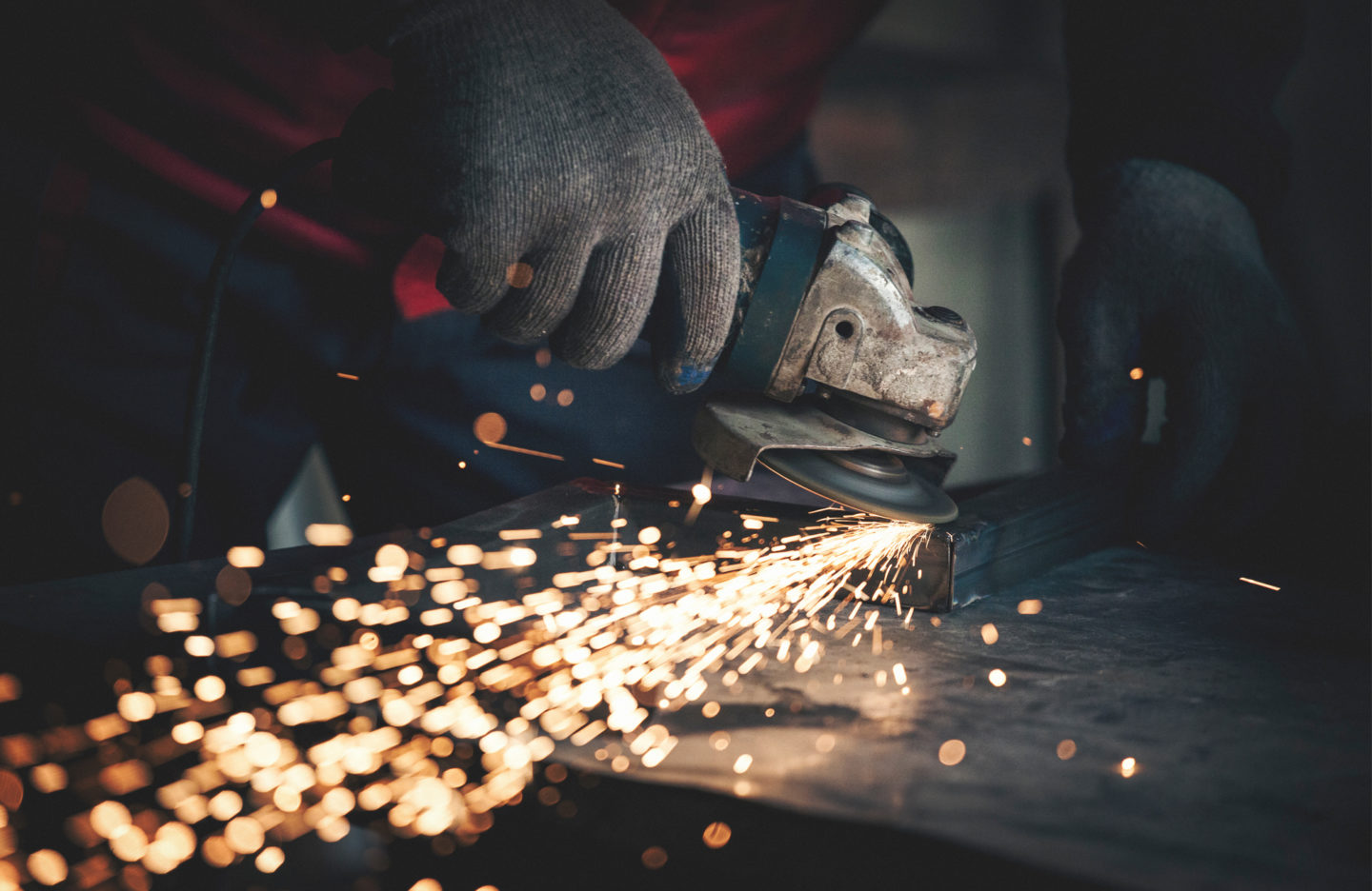 Worker grinding and welding metal with sparks flying