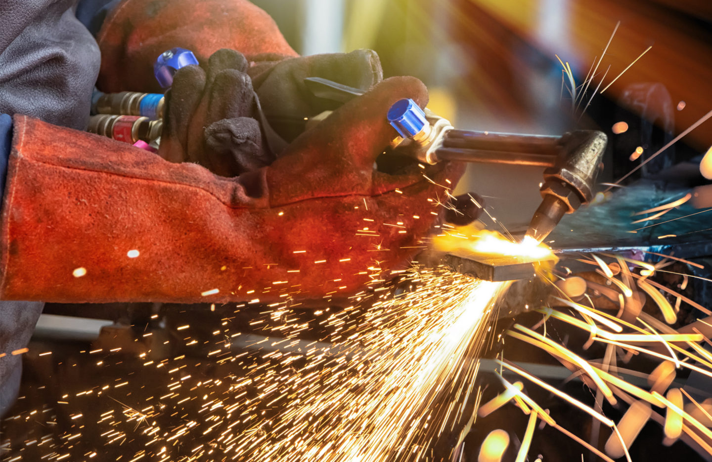 person with a cutting torch welding in a factory