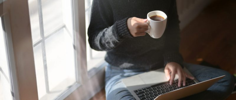 Woman working from home with coffee and laptop